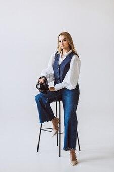 Une belle femme photographe dans une tenue décontractée en denim et un chemisier blanc avec des manches volumineuses avec un appareil photo dans ses mains. passe-temps. mise au point sélective douce.