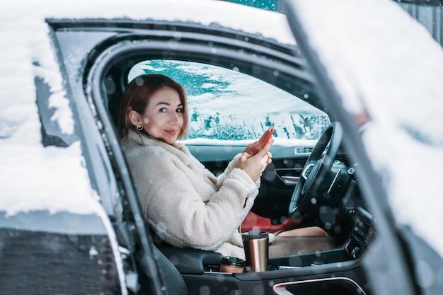 Belle femme pilote nsitting au volant de sa voiture