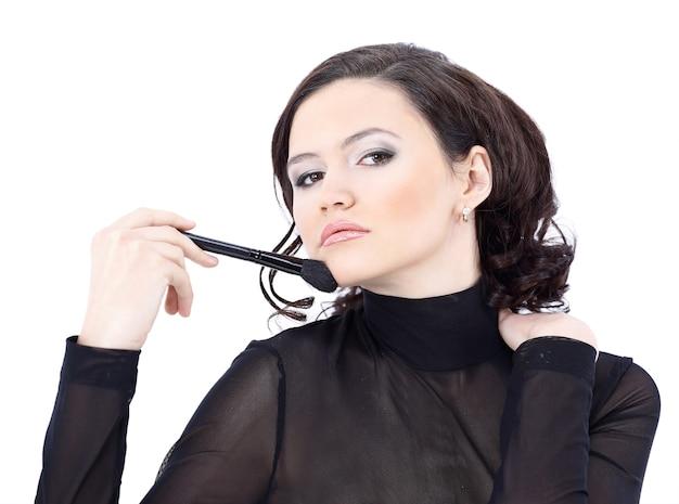 Belle femme avec pinceau de maquillage près de son visage isolé sur blanc