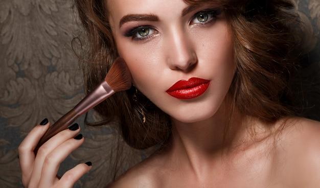 Belle femme avec un pinceau de maquillage