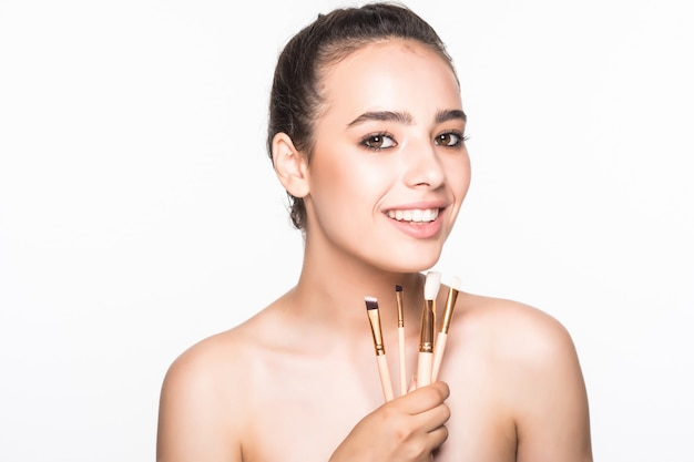 Belle femme avec des pinceaux de maquillage près de son visage isolé sur mur blanc
