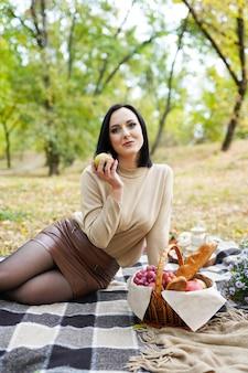 Belle femme en pique-nique d'automne avec des fleurs, des feuilles d'automne et de la citrouille, vacances de thanksgiving