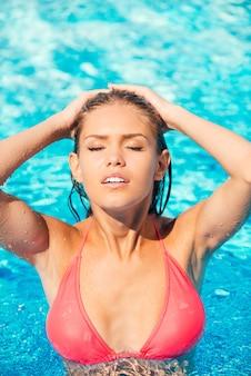 Belle femme à la piscine. vue de dessus de la belle jeune femme en bikini ajustant ses cheveux mouillés et gardant les yeux fermés en se tenant debout à la piscine