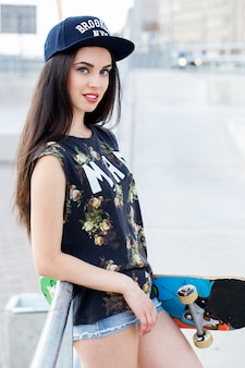 Belle femme avec planche à roulettes posant dans la rue