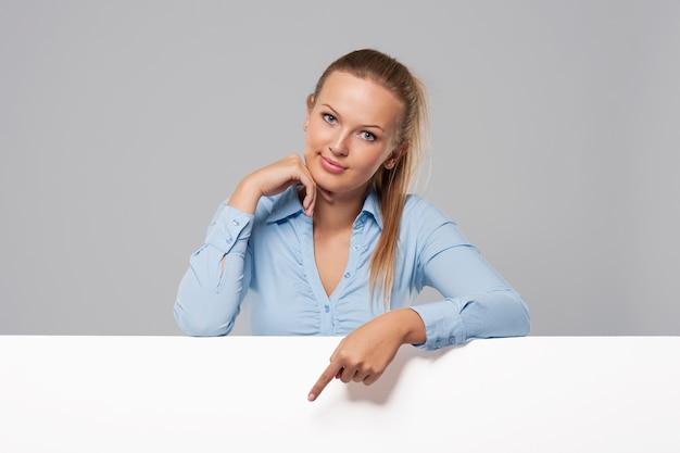 Belle femme pointant sur tableau blanc