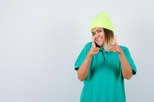 Belle femme pointant vers l'avant en t-shirt polo, bonnet et l'air heureux. vue de face.