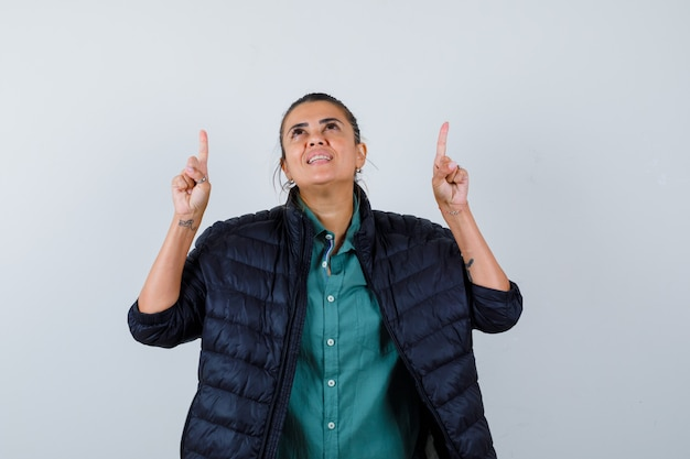 Belle femme pointant vers le haut avec les index en chemise verte, veste noire et à la gaieté. vue de face.
