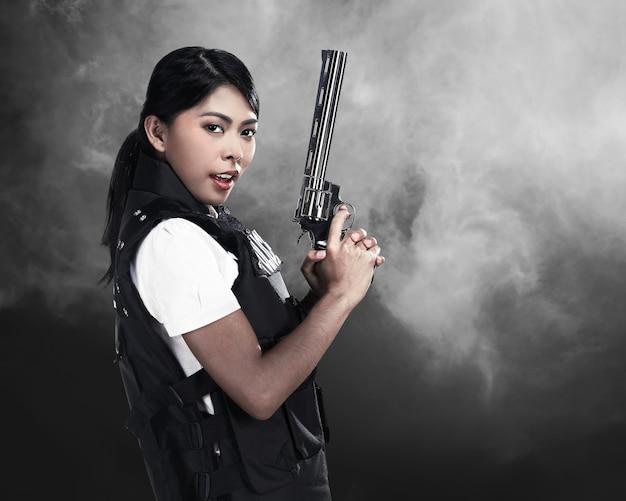 Belle femme de police tenant un fusil