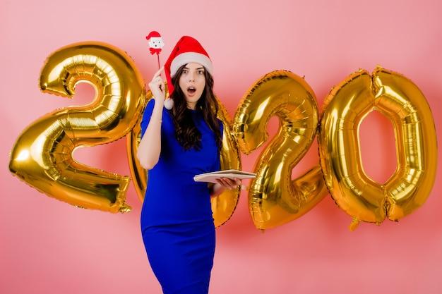 Belle femme portant bonnet de noel écrire des notes dans le cahier devant des ballons du nouvel an 2020 isolés sur rose