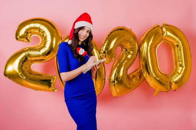 Belle femme portant bonnet de noel écrivant des plans dans le cahier devant des ballons de la nouvelle année 2020