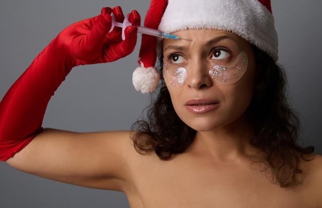 Une belle femme portant un bonnet de noel et des gants rouges tient une petite seringue et fait une injection de beauté sur son front. traitement anti-âge, concept de rajeunissement pour la publicité de noël pour les salons de spa