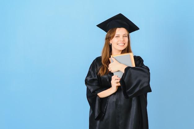 Belle femme portant une casquette de graduation et une robe de cérémonie tenant un diplôme à la recherche de positif et heureux debout et souriant avec un sourire confiant.