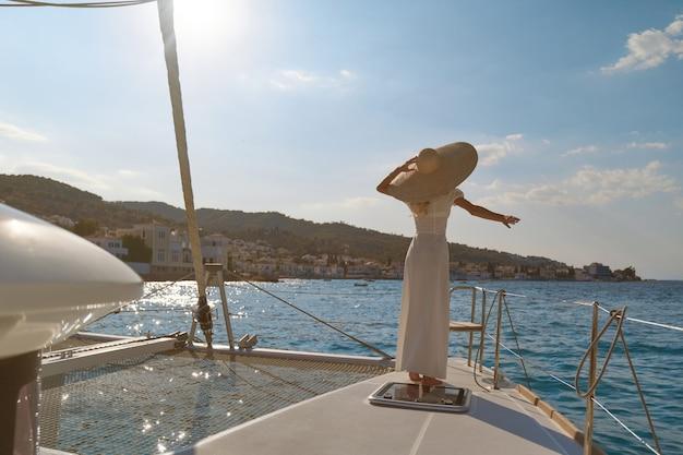 Belle femme portant un chapeau de paille et une robe blanche sur un yacht profite du voyage, spetses, grèce, europe.