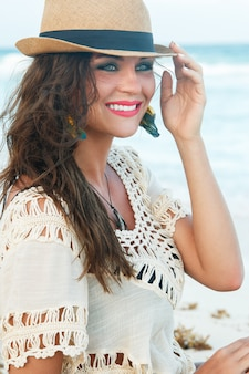 Belle femme portant un chapeau sur la plage
