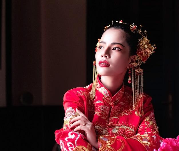 La belle femme portant un costume rouge, tournez le visage vers le haut à l'extérieur, portrait de modèle posant sur le festival du nouvel an chinois