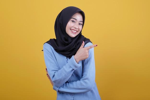 Belle femme portant le hijab avec pointant vers la gauche regarde joyeusement l'expression