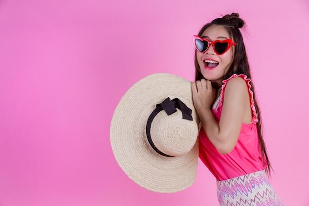 Une belle femme portant des lunettes rouges avec un grand chapeau sur un rose.