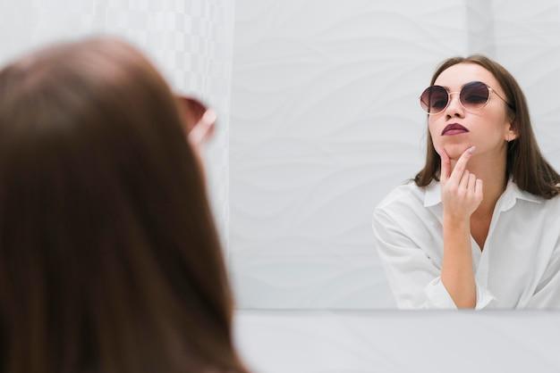 Belle femme portant des lunettes de soleil dans la salle de bain