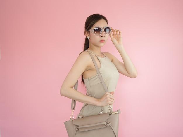 Belle femme portant des lunettes de soleil et portant des sacs en cuir, concept de mode