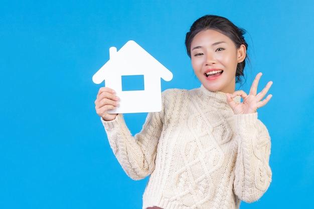 Une belle femme portant une nouvelle chemise blanche à manches longues avec un symbole de la maison. commerce de maison.