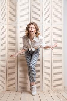 Belle femme portant un pantalon et une chemise dansant devant une jalousie