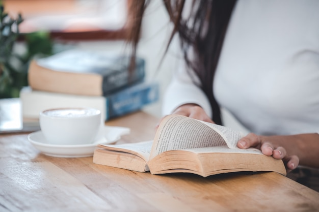 Belle femme portant un t-shirt blanc lisant une table en bois dans une pièce blanche