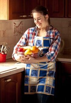 Belle femme portant un tablier tenant un bol frais avec des fruits
