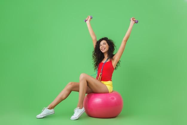 Belle femme portant des vêtements d'été soulevant des haltères alors qu'elle était assise sur un ballon de fitness pendant l'aérobic contre le mur vert