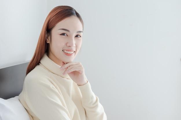 Belle femme porter jaune pull sourire dans sa chambre
