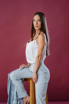 Belle femme posant sur une chaise. mode.
