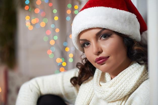 Belle femme posant chaudement coiffée d'un chapeau de noël.