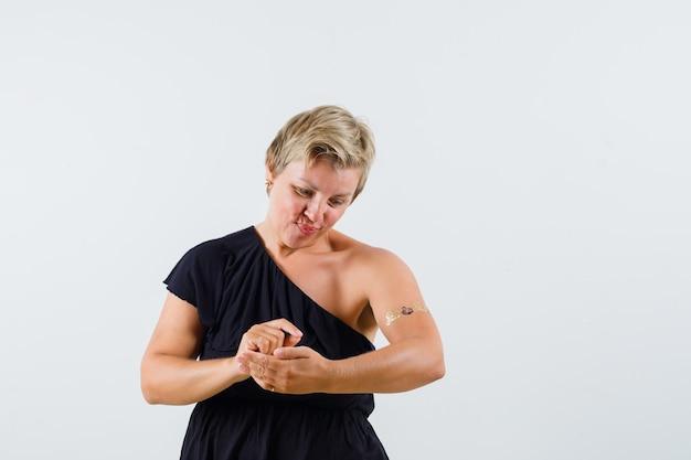 Belle femme posant comme écrire avec un stylo sur papier en chemisier noir et à la recherche concentrée