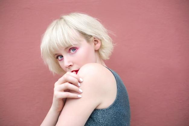 Belle femme posant devant un mur rose