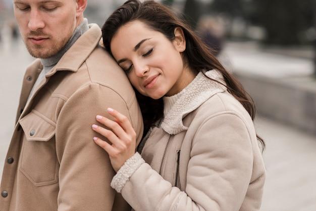 Belle femme posant avec l'homme à l'extérieur