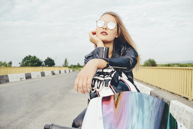 Belle femme posant avec des lunettes de soleil sur une moto