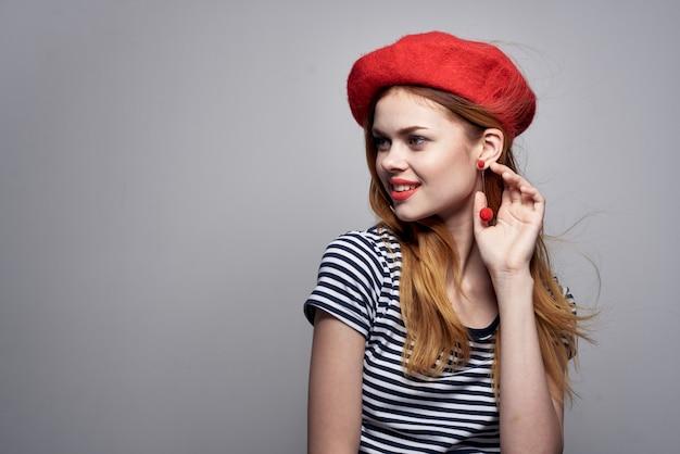 Belle femme posant mode look attrayant boucles d'oreilles rouges bijoux fond clair