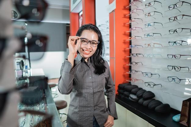 Une belle femme posant portant des lunettes d'une vitrine de lunettes dans une clinique ophtalmologique