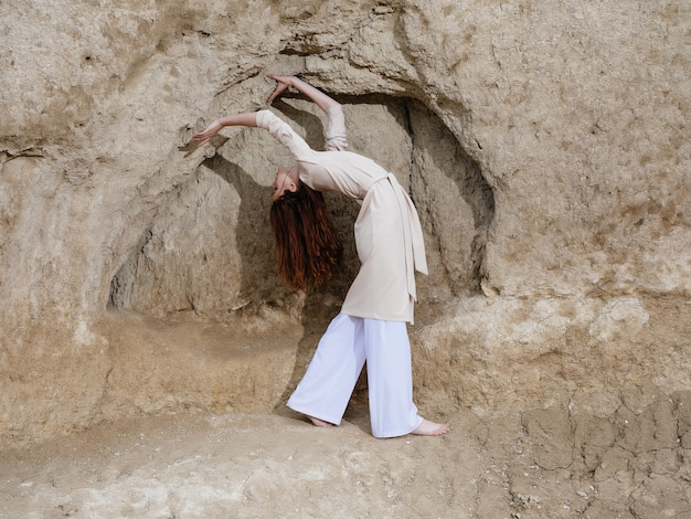 Belle femme posant près des rochers dans le modèle de sable voyage. photo de haute qualité