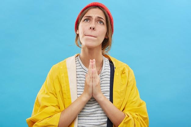 Belle femme posant en studio bleu en gardant les mains pressées ensemble