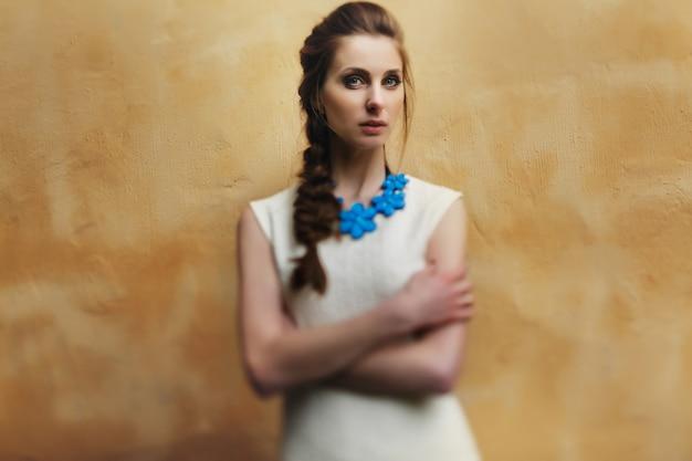 Belle femme pose devant le mur jaune