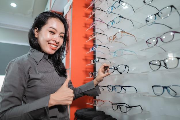 Une belle femme pose tenant des lunettes dans une fenêtre dans une clinique ophtalmologique