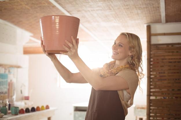 Belle femme potter vérifiant le pot