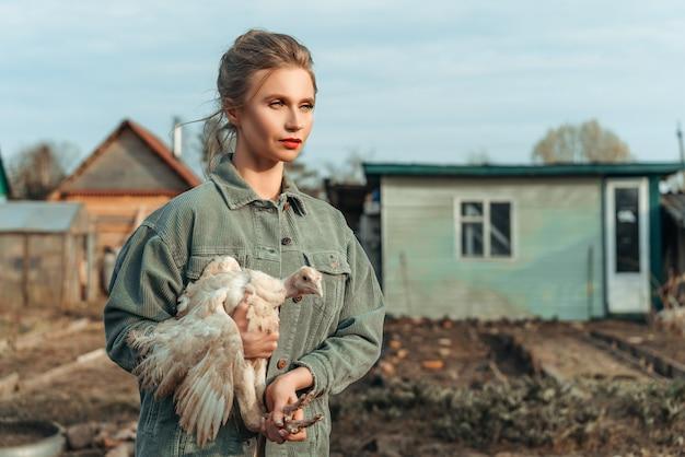 Belle femme avec un poulet dans ses mains