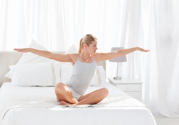 Belle femme pratiquant le yoga sur son lit