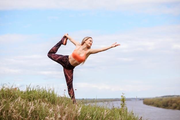Belle femme pratique le yoga en plein air.