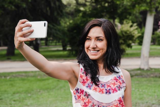 Belle femme prenant une photo d'elle-même, selfie