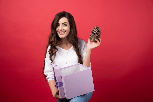 Belle femme prenant une pomme de pin dans une boîte cadeau violette. photo de haute qualité