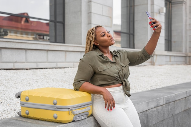 Belle femme prenant un selfie à côté de ses bagages