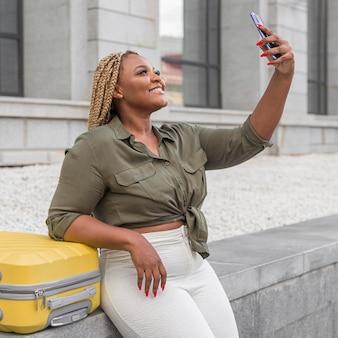 Belle femme prenant un selfie à côté de son bagage jaune