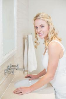 Belle femme prenant soin d'elle-même dans la salle de bain
